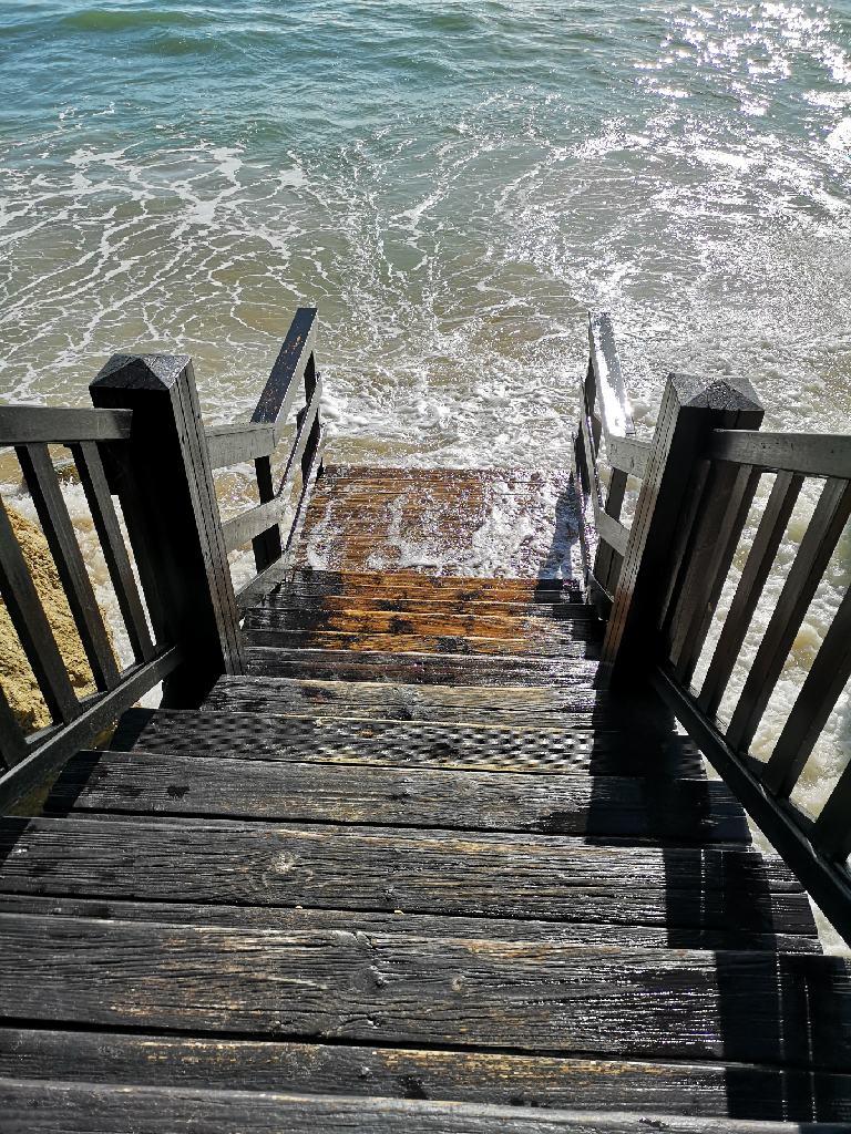 Die Flut umspült die Treppe zum Strand
