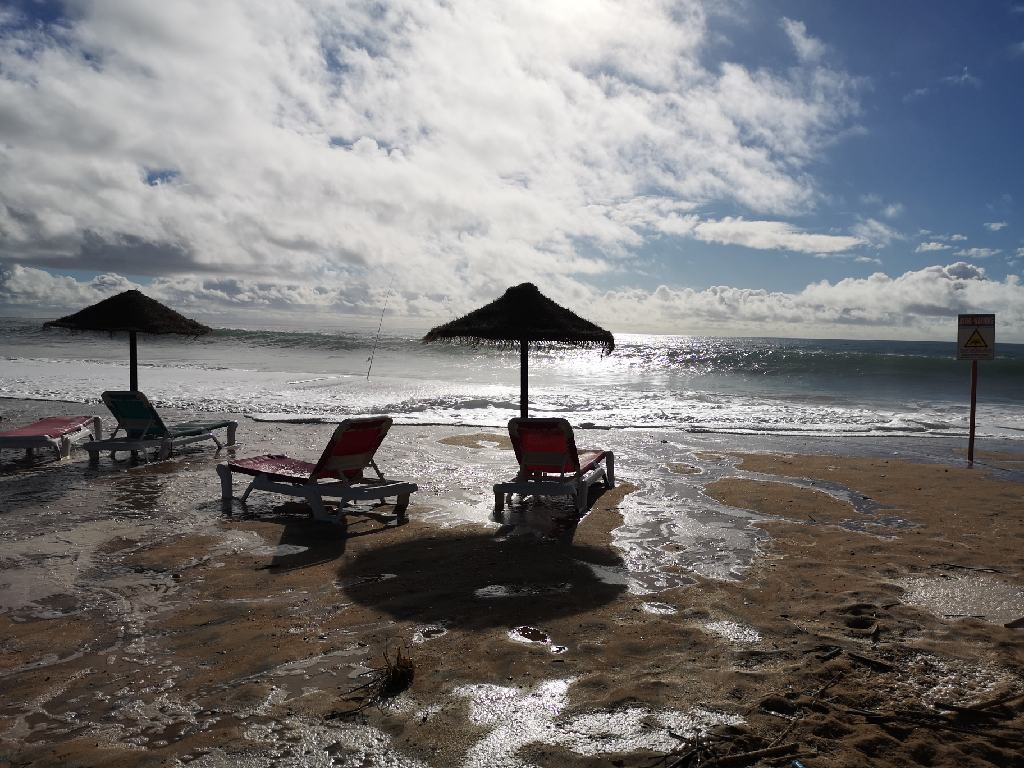 Liegestühle vom Wasser verstellt am Praia do Almargem